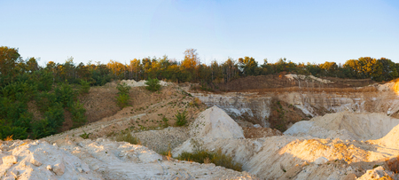 slice of a sand dump quarry dunes waves sand stones sky clouds bushes trees green grass texture