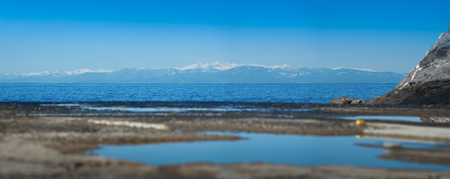 blue sea in the reflective sky and view of mountains snow hills at background at the pier