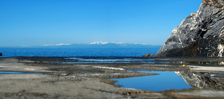 Reflective blue sky in water at pier and snowly mountains