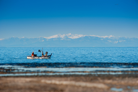 Winter view of the sea with covered snow Mountains and the fishing boat Stock Photo