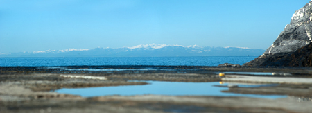 Reflective blue sky in water at pier and snowly mountains background Stock Photo