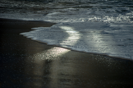 sea wave running in the evening at sunset on a black pebble like a iceland beach