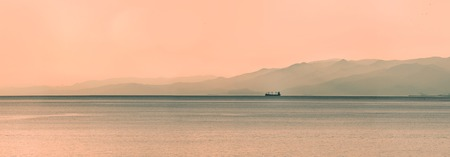 Panoramic view of ship at sunset with mountains