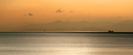 Panoramic view of ship at orange sunset with mountains siluets