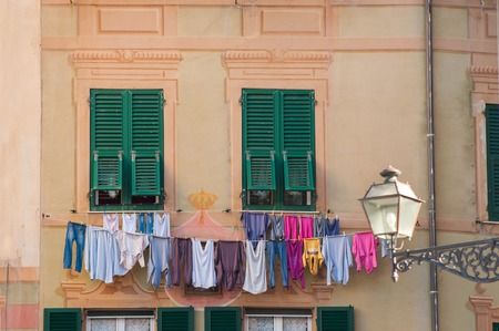 colorful old facade with dry clothes in small village Camogli Stock Photo
