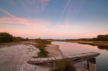 Lake with masonry on the shore panoramic view on evening pink light, Ukraine