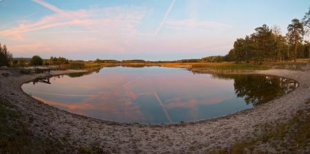 Lake with sandy shore panoramic view on evening pink light, Ukraine Stock Photo