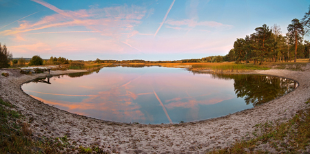 Lake with sandy shore panoramic view on evening pink sky