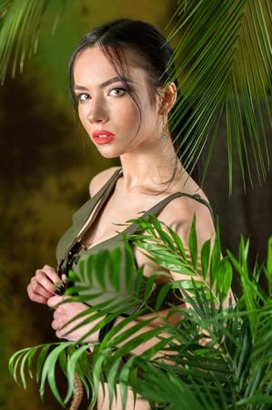 Un retrato de niña con hojas de palma vestida como una mujer cosplay en la selva