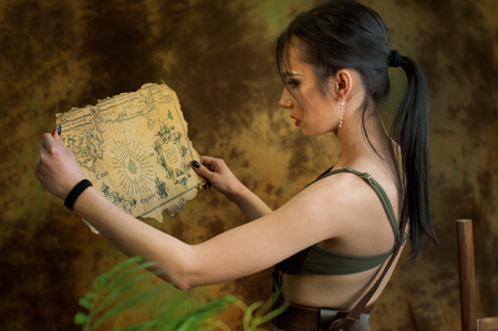 A young girl dressed up as a cosplay woman in jungle discovery old map with treasures Archivio Fotografico