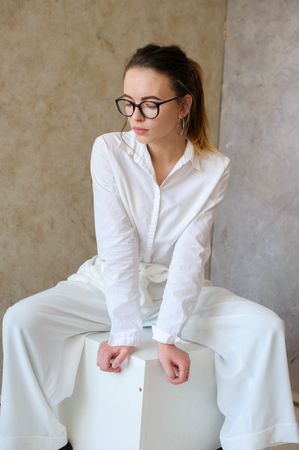 women in white fashion clothes seat on cube Stock fotó