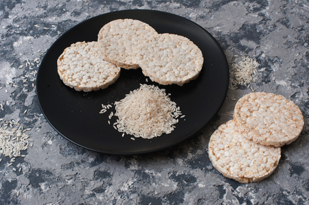 stack of puffed rice bread slices on black plate on textured background