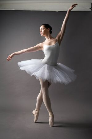 A young graceful ballerina dressed in a white tutu, demonstrates dance skills pose