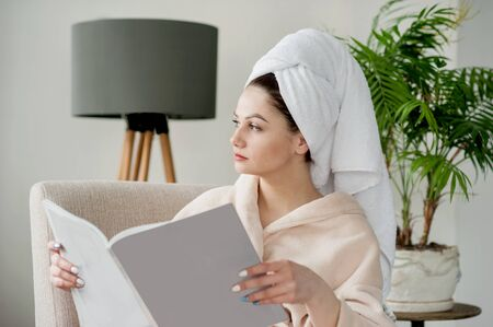 Portrait of beautiful girl in bathrobe spa relaxation wearing bathrobe and towel on head after shower.