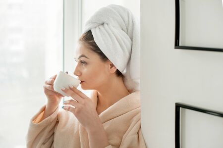 Young girl with a towel on her head is drinking with cup cofee, near window sill in the bathroom