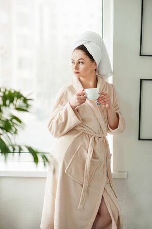 Attractive young girl in bathrobe and with a towel on her head is holding a cup, sitting on a window sill in the bathroom Stock Photo