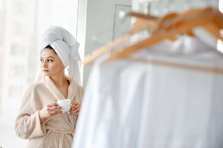 Portrait girl with towel on head near window with a cup of cofee, home style relaxation concept after shower. Stock Photo