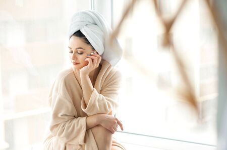 Portrait of beautiful girl and towel on head in bathrobe with a cup, home style relaxation concept after shower.