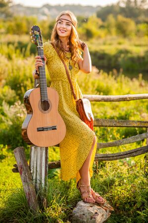 bohemian woman holding guitar on field near wooden fence in warm sunset light