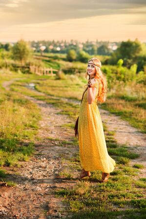 Happy girl in bohemian style yellow dress with guitar on the field turned back at sunset