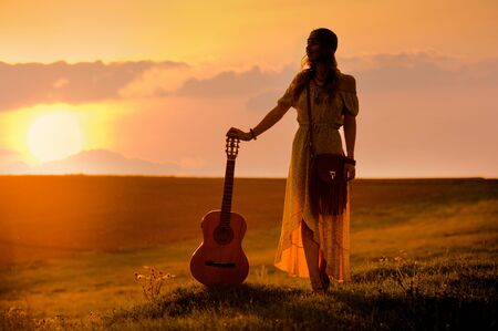 siluette of woman wearing a bohemian style holding a guitar on a field at warm light of sunset 写真素材 - 132096468