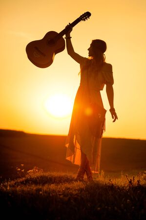 siluette of woman wearing a bohemian style holding a guitar on a field at warm light of sunset