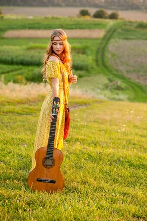 Smiling bohemian girl in yellow dress with guitar on the field is back at sunset