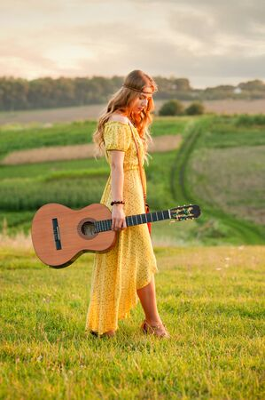 girl in yellow dress bohemian style, holding a guitar on the field with a warm and comfortable atmosphere sunset