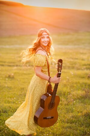 Beautiful hippie girl with guitar dancing on field at sunset