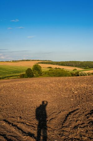 hills are agricultural land, plowed land and a wheat field with shadows silouette man on the ground