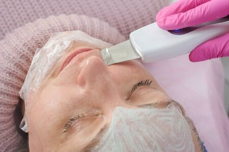 procedure of face cleaning by ultrasonic device close up with antibacterial mask