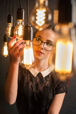 Vintage incandescent Edison type bulbs. girl in retro style with glasses, science and study Banque d'images - 140030768
