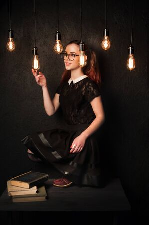 Retro-style girl wearing glasses and tights with glasses examines the glow of edison lamps. Banque d'images - 140030771