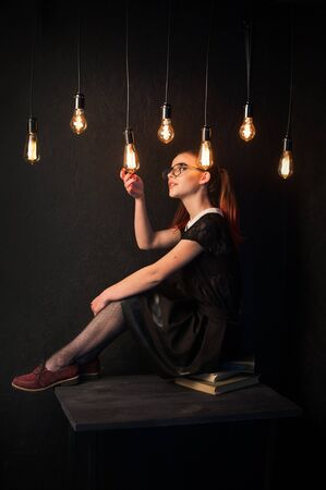 examines the glow of edison lamps. Girl in retro style with glasses with tails and hamstrings Banque d'images - 140030772