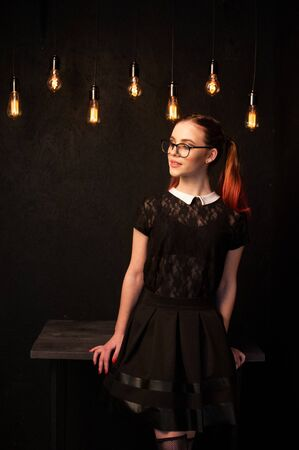 Cute school girl against black wall with bulbs hanging above Banque d'images - 140030774
