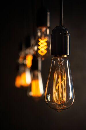 Vintage incandescent Edison type bulbs on dark wall background