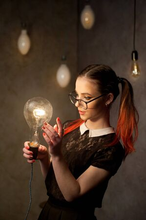 schoolgirl in glasses with idea lamp on lamp background Banque d'images - 140030782