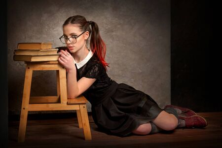 Beautiful girl in retro school uniform holds books in old library. Beauty, fashion. Educational concept. Banque d'images - 140030684
