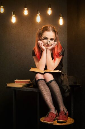Creative student in glasses and hamstrings, reading book sitting with illuminated edison lamps on the background Banque d'images - 140030689