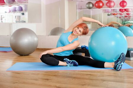 smiling girl training with fitness ball in gym Stock fotó