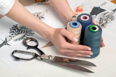 clothing designer hands holding spools of thread and seamstress scissors