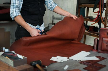 Master sewing leather goods, concept of handmade craft production of leather goods. Stockfoto