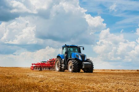 blue tractor working in the field, agricultural machinery work, field and beautiful sky