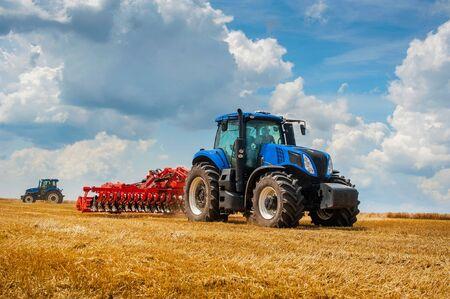 blauer neuer Traktor mit roter Egge im Feld gegen einen bewölkten Himmel, Landmaschinen arbeiten