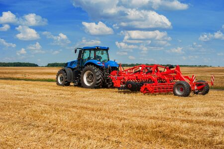 blue tractor with pulls red harrow working in a field, ready to sowing, sowing campaign