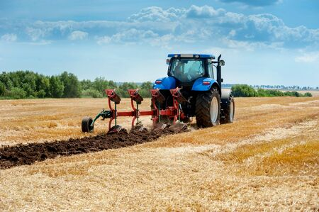 blue tractor with red plow, arable land, field preparation