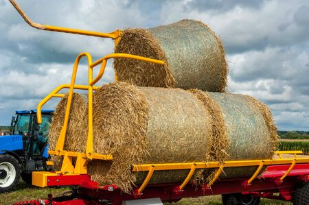 Straw on a trailer from a tractor in a field on a sunny day