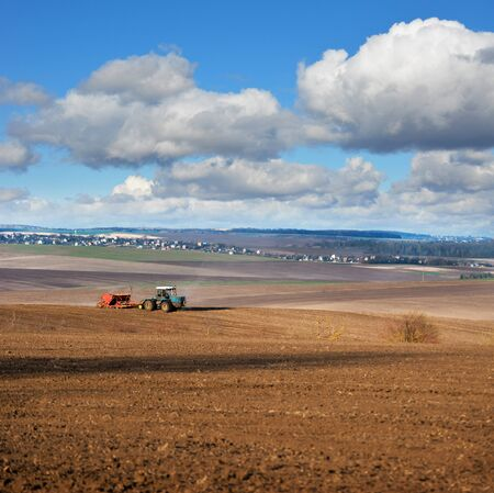 panoramic view of plowed field, tractor with seeder, beautiful sky with clouds. agricultural land, it is time to sow