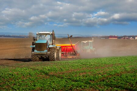 tractors sowing in the field, cloud of dust. Agricultural tillage, prepare the land, tractor with a seeder, sow