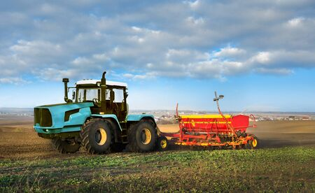 Big tractor cultivated soil on fields Ukraine at spring. Farmers prepare the land, tractor with a seeder, sowing time